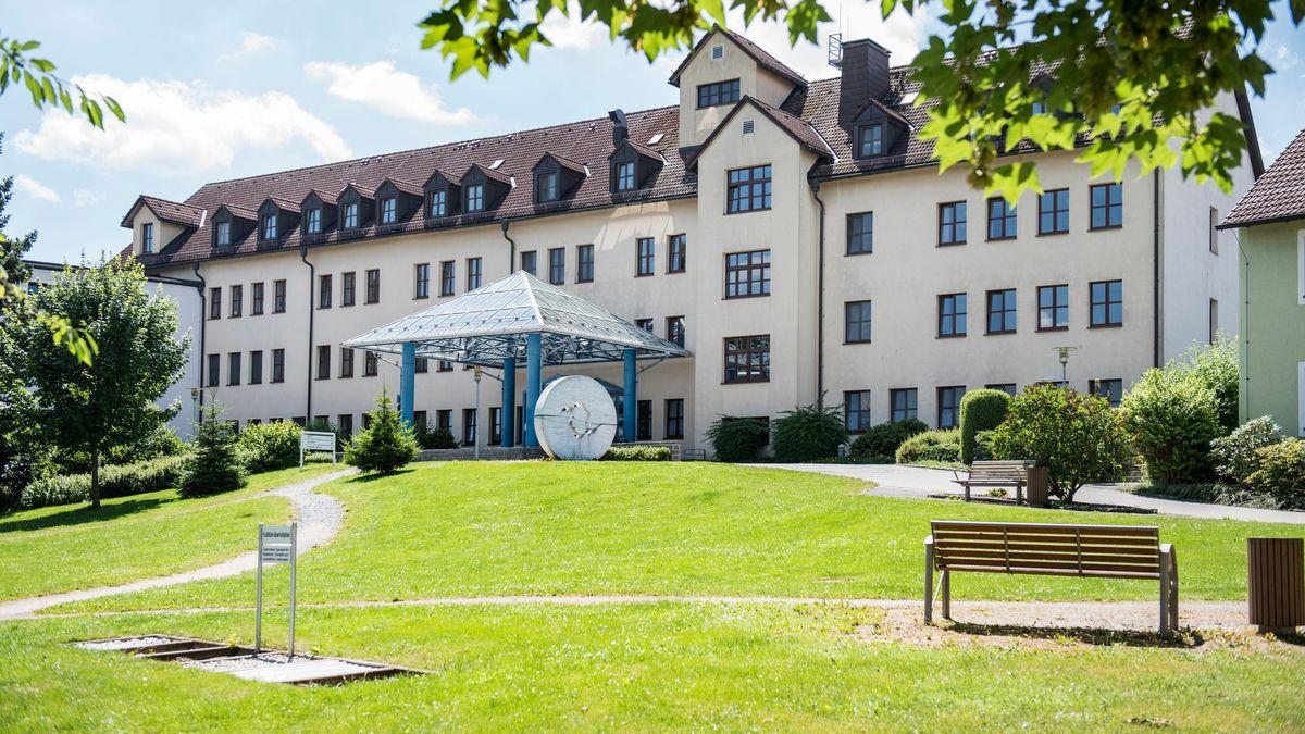 Die bestehende Klinik des Bezirks Oberfranken in Rehau liegt im Grünen, davor eine Wiede mit Sitzbänken.