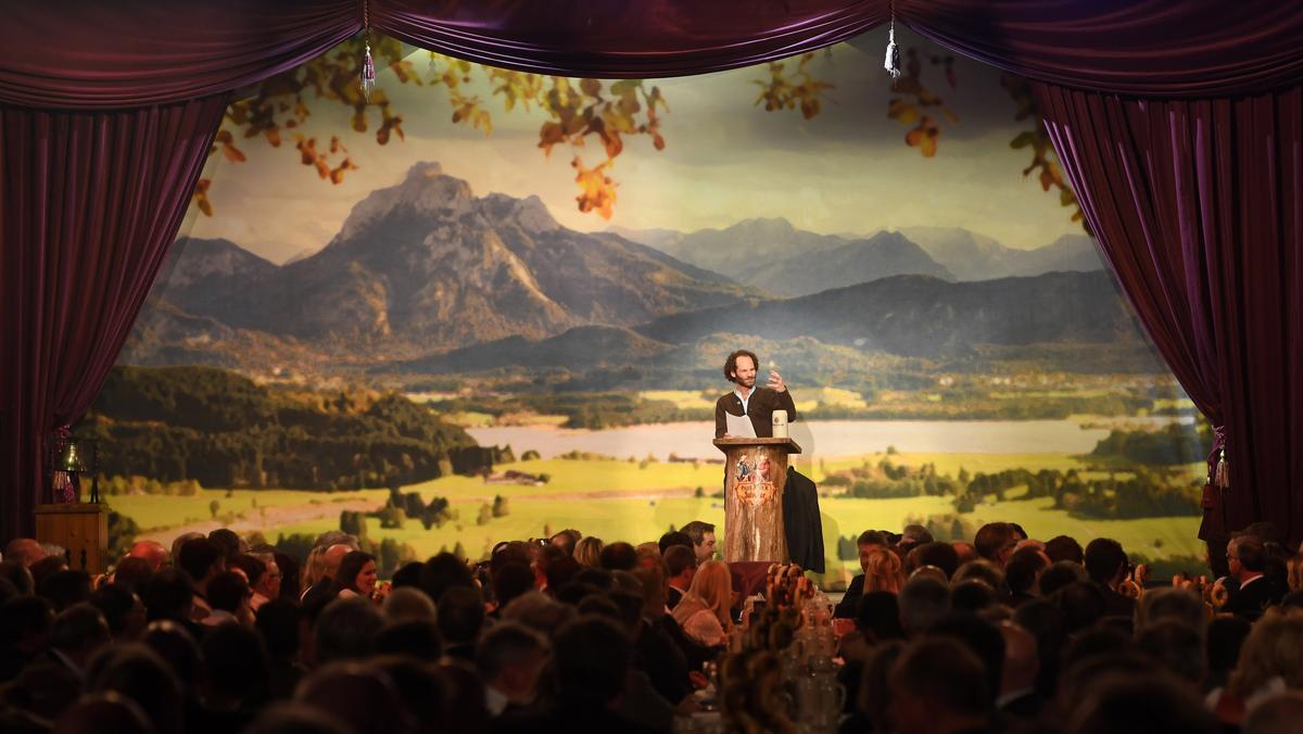 Ein Mann steht auf der Bühne und spricht zu einem Publikum.