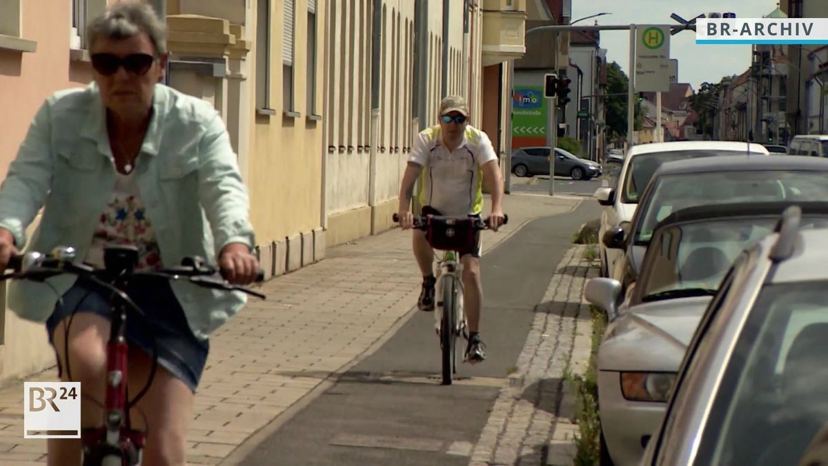 Zwei Radfahrer sind auf einem Radweg unterwegs, daneben parken Autos.