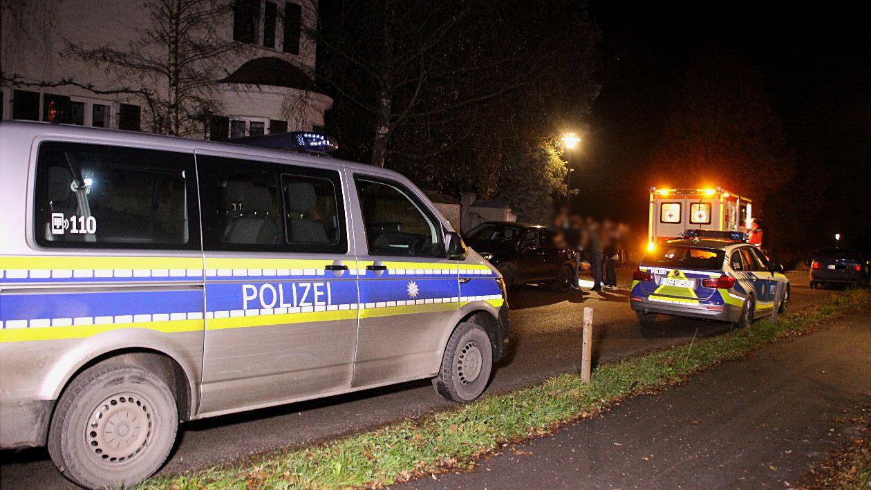 Polizeifahrzeuge und Rettungswagen vor einem Haus in Albaching; Gäste auf dem Gehweg.