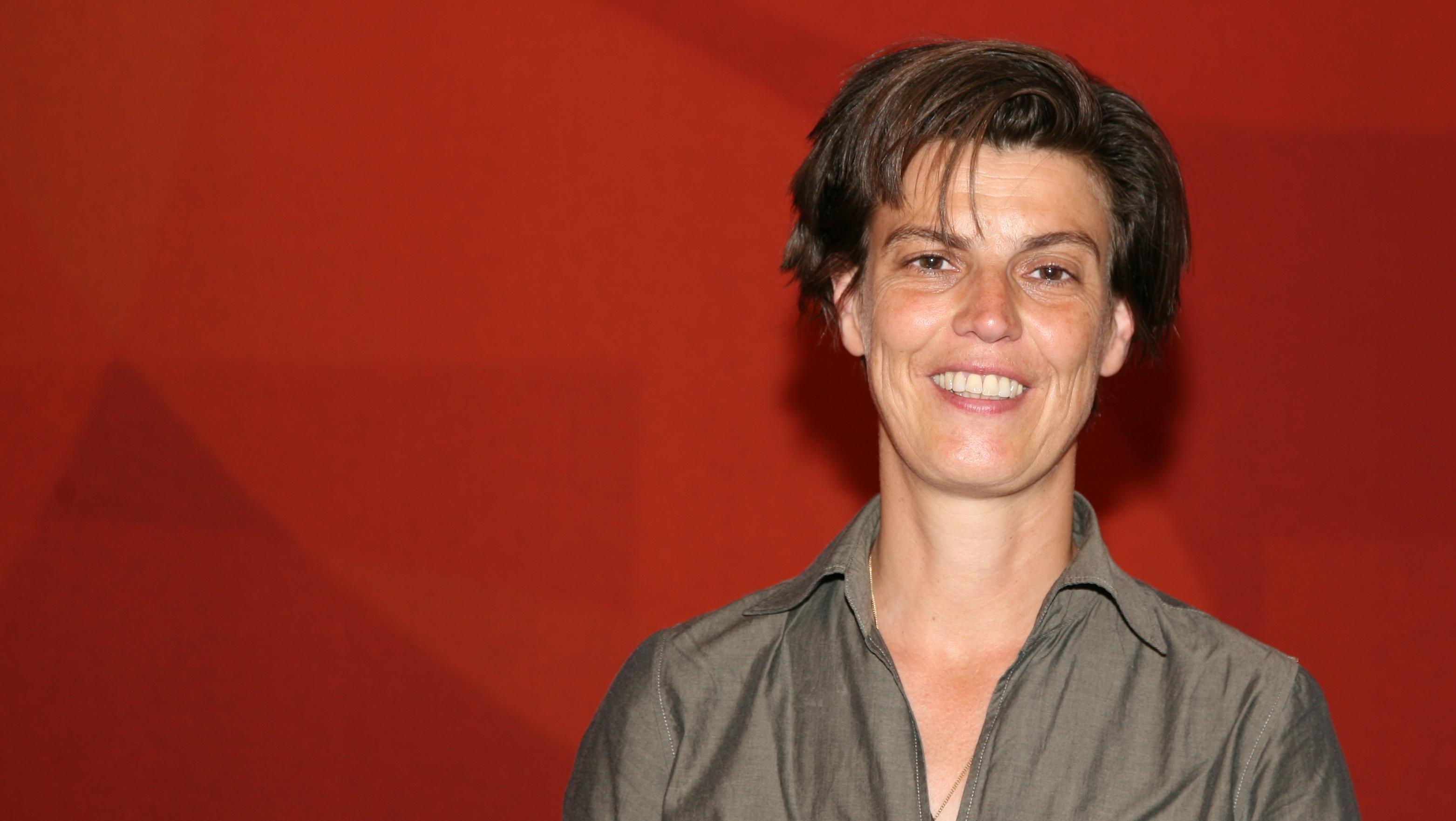 Carolin Emcke lächelnd vor einer roten Wand.