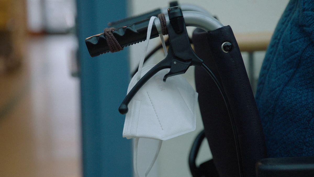 Eine Schutzmaske hängt über einem Rollstuhl-Griff