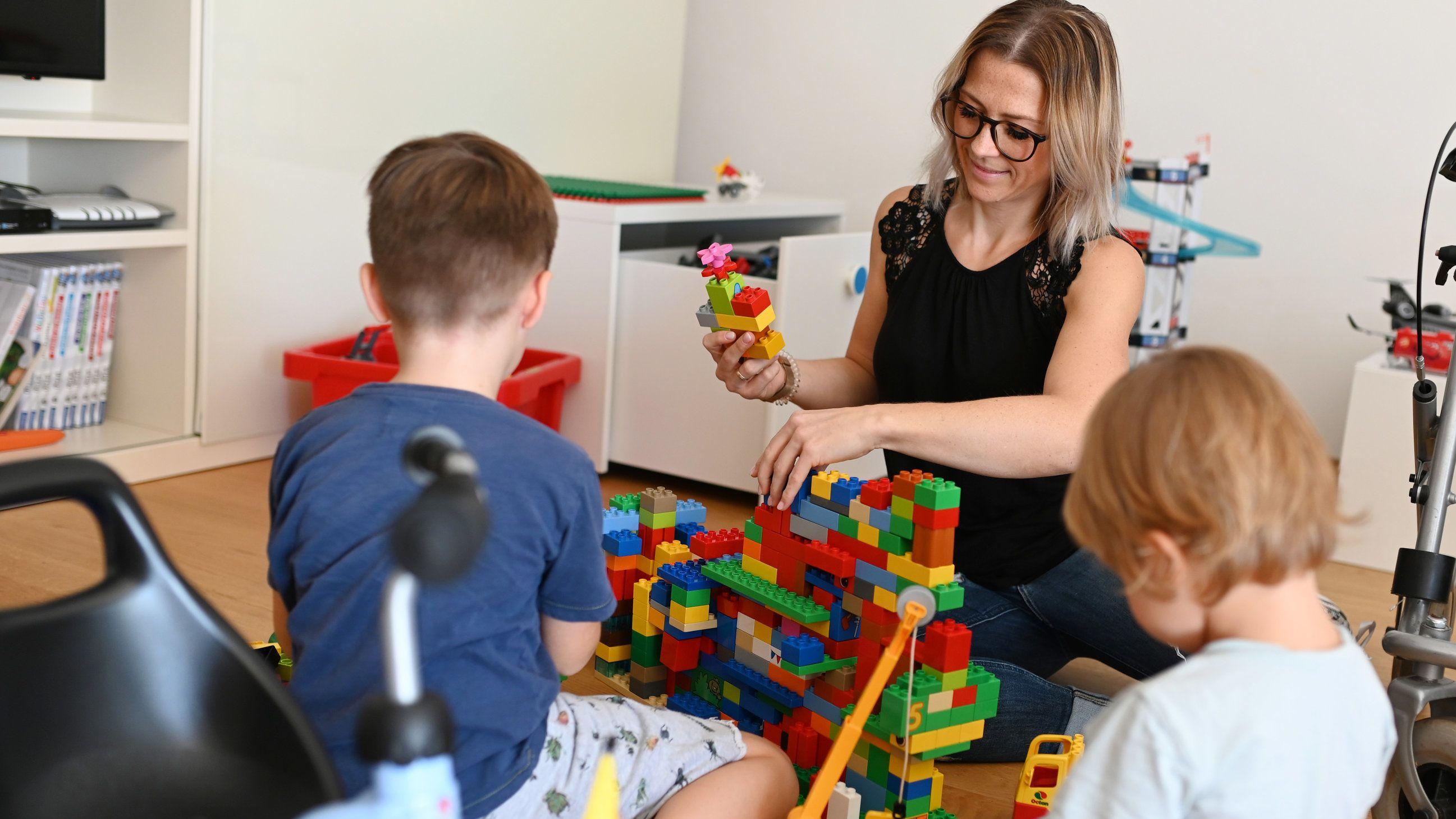 Zwei Kinder sitzen mit einer Frau in einem Zimmer am Boden und bauen einen Turm aus Duplo.