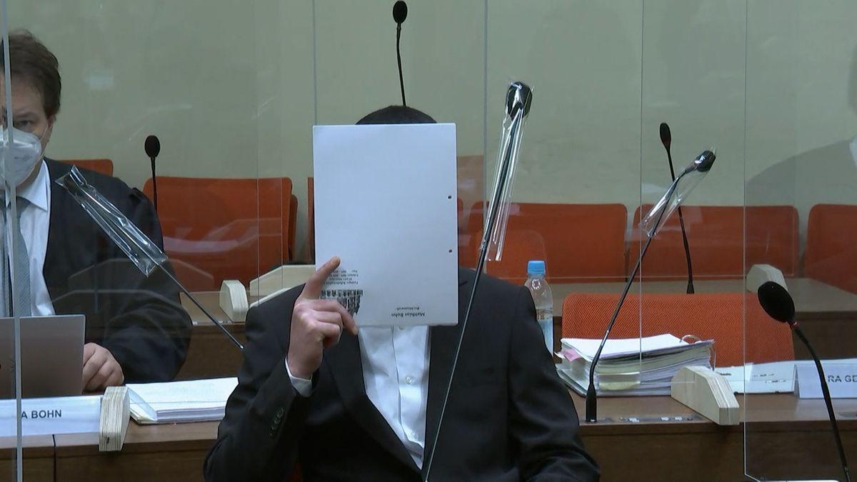 Angeklagter verbirgt sein Gesicht hinter einem Blatt