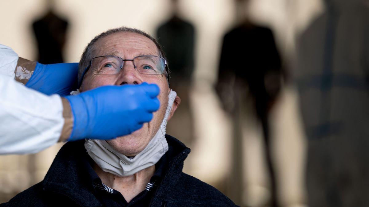 Arzt nimmt für einen Corona-Test einen Rachenabstrich von einem älteren Mann