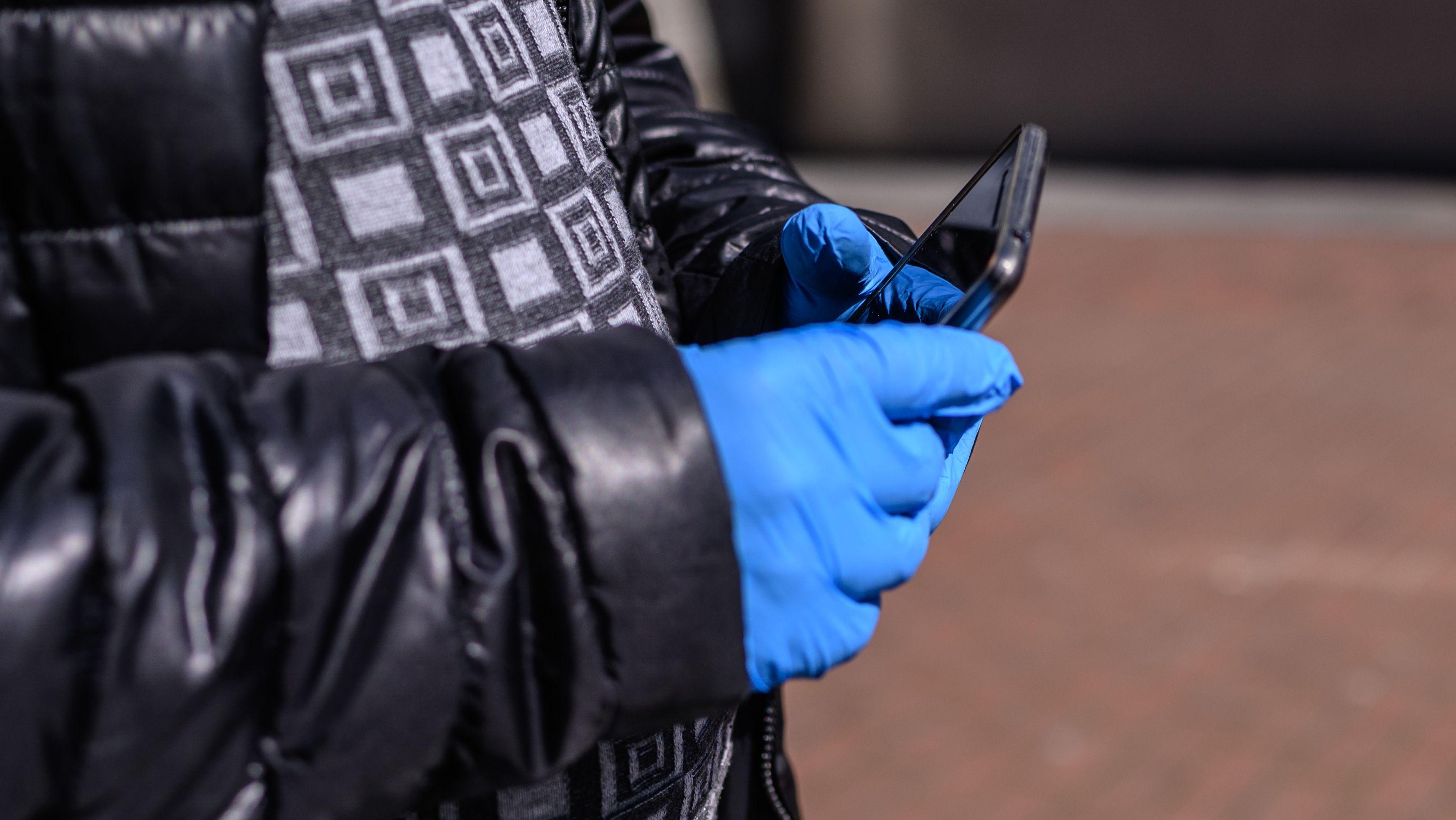 Person mit Schutzhandschuhen hält Smartphone