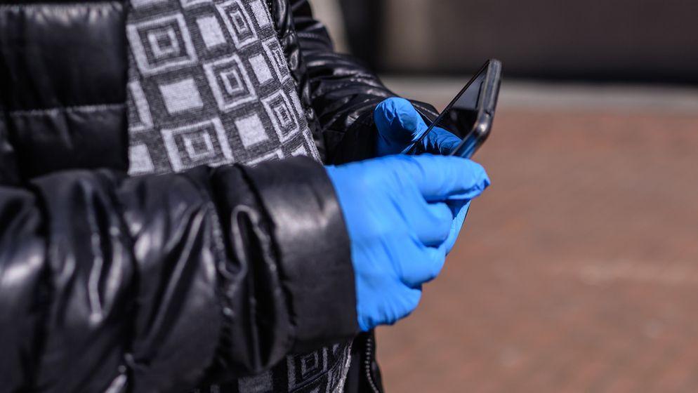 Person mit Schutzhandschuhen hält Smartphone | Bild:Edith Geuppert/Picture Alliance