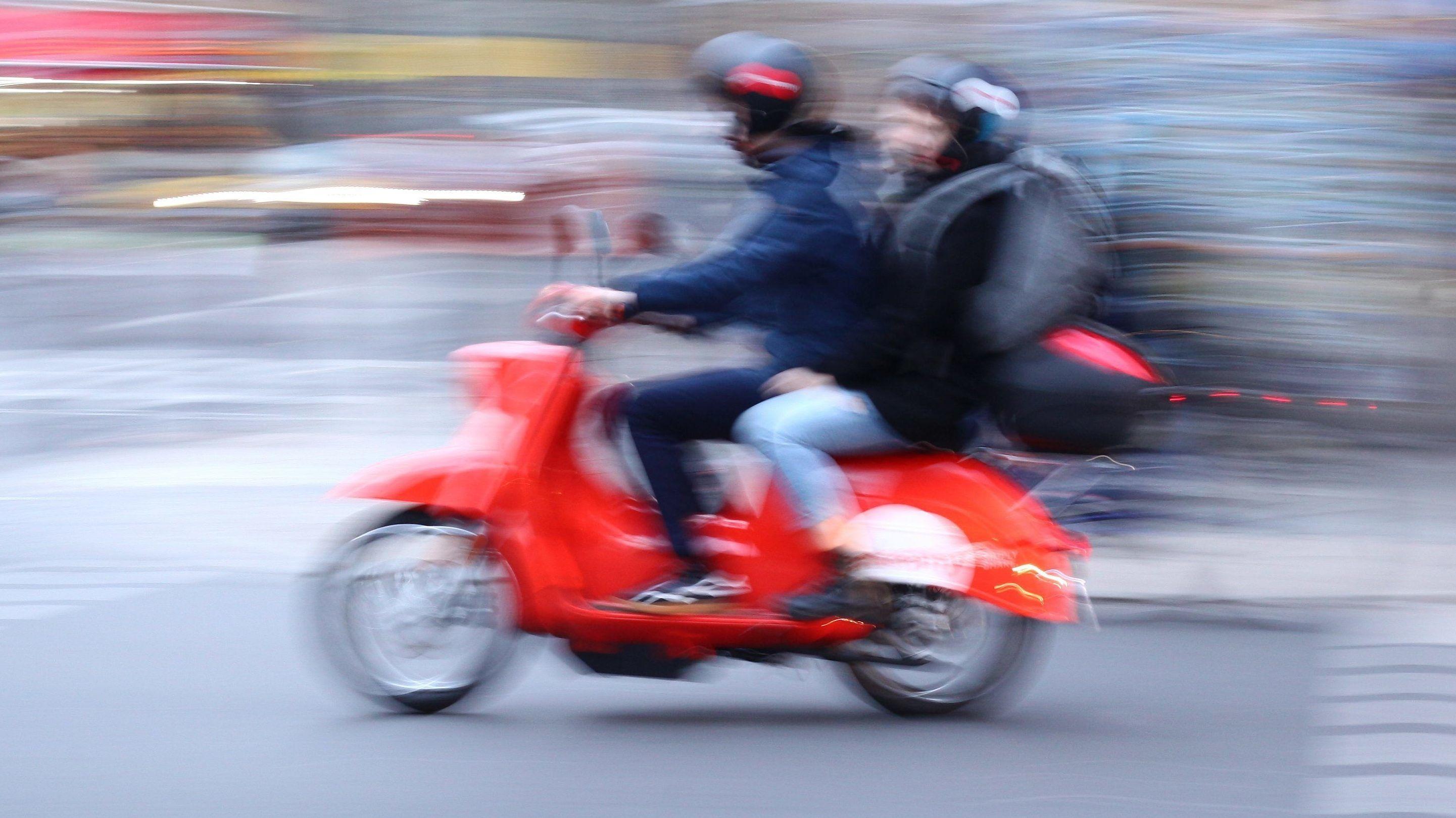 Ein junger Mann und eine junge Frau auf einem Motorroller