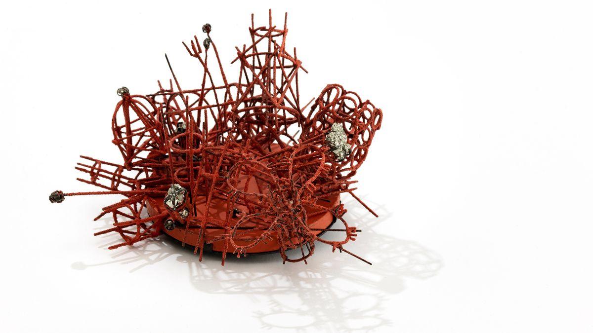 Rote Brosche mit flexiblen Einzelteilen aus gelötetem Eisendraht auf einem Scheibenmagnet
