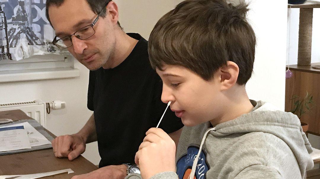 In Österreich schon erprobt: In Wien führt ein Junge unter der Aufsicht seines Vaters einen Corona-Selbsttest durch.