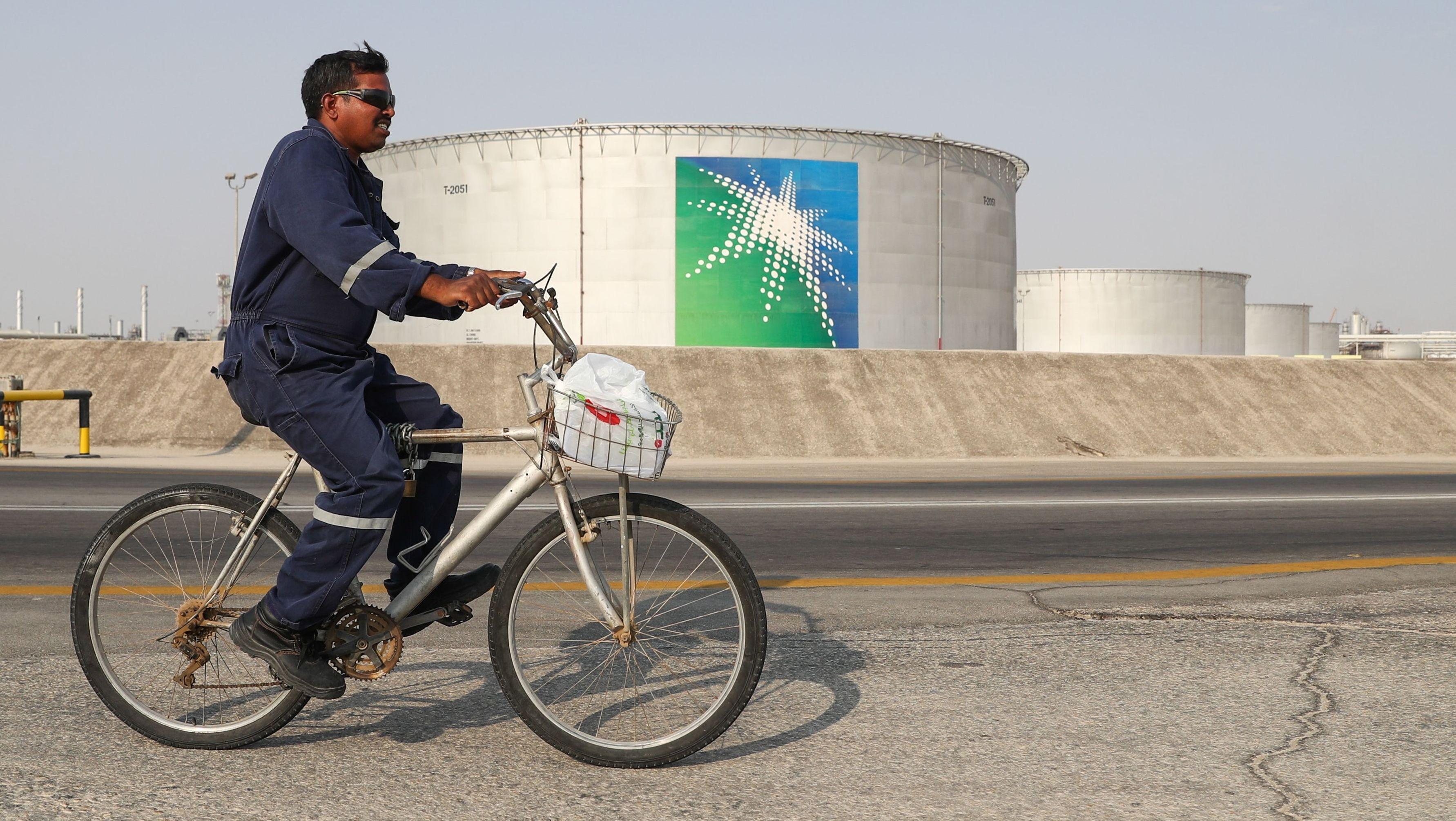 Ein Arbeiter vor Öltanks des Unternehmens Saudi Aramco