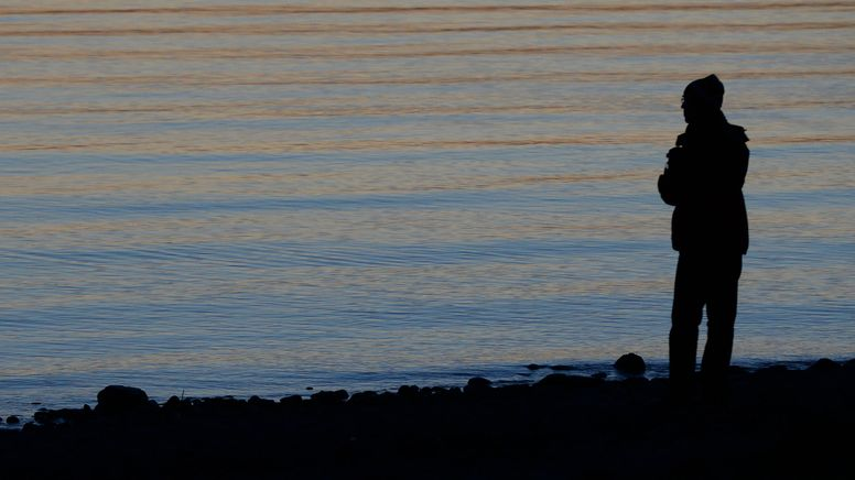 Ein Mann steht am Abend am Ufer eines Sees (Symbolbild).   Bild:dpa-Bildfunk/Felix Kästle