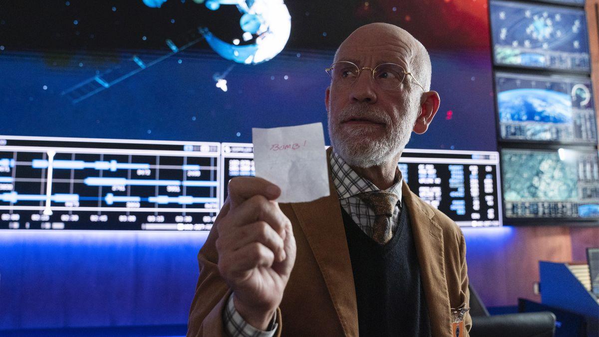 John Malkovich alias Adrian Mallory steht vor Bildschirmen mit Zahlen und Ansichten aus dem All, hält einen Zettel mit einer Notiz hoch.