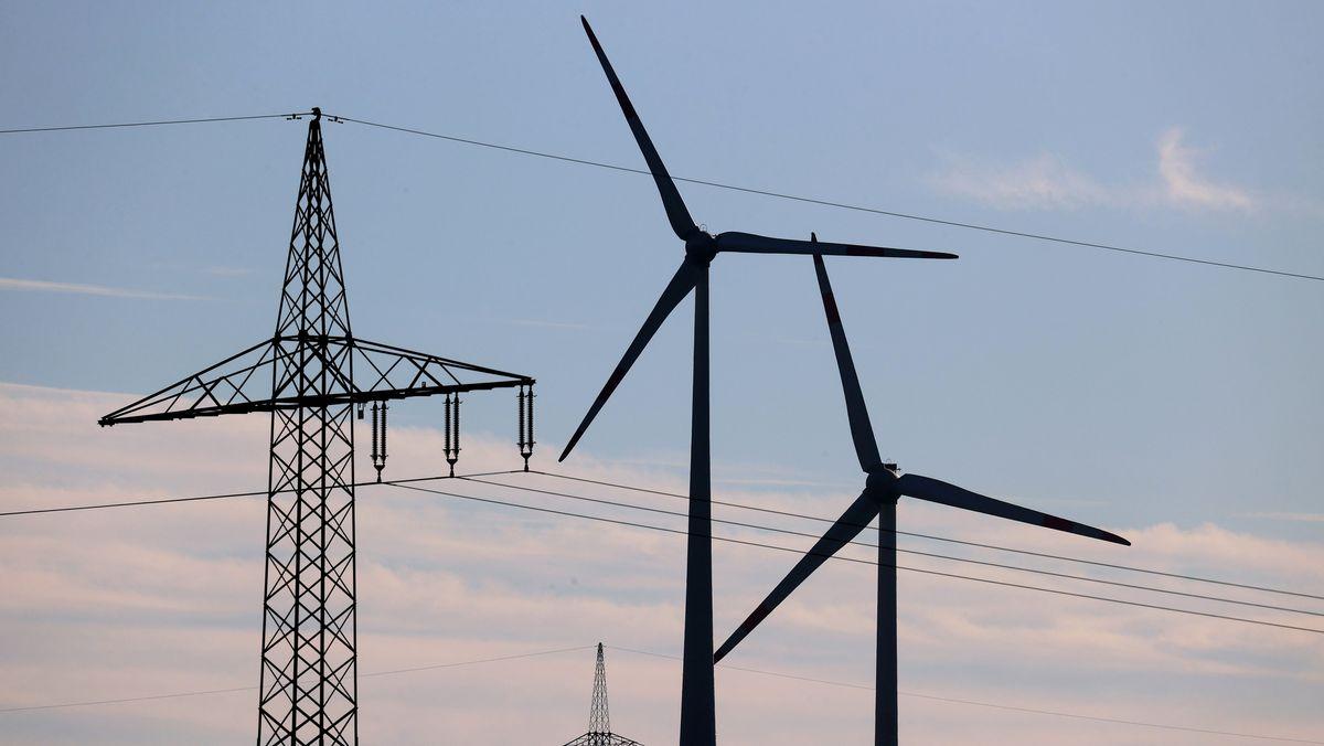 Bayern, Biebelried: Windräder stehen vor den Masten einer Stromtrasse