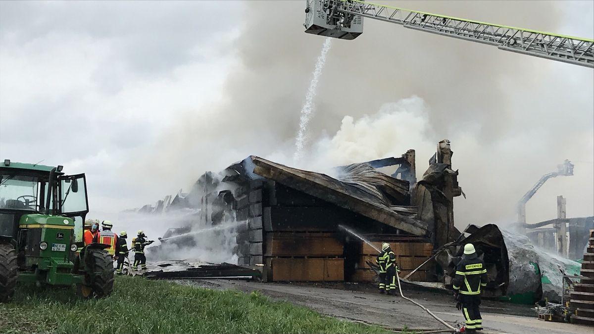 Zahlreiche Feuerwehrleute spritzen Wasser auf das Gebäude eines holzverarbeitenden Betriebs in Burgbernheim.