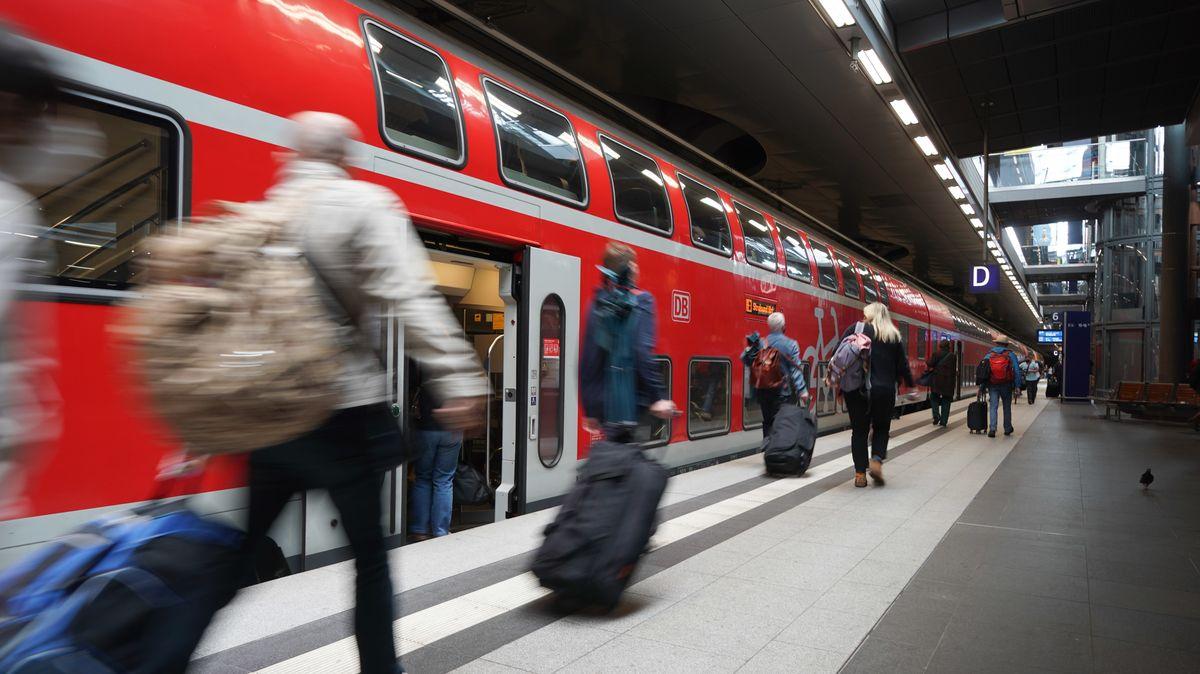 Zugreisende am Bahnsteig vor einem Regionalexpress-Zug