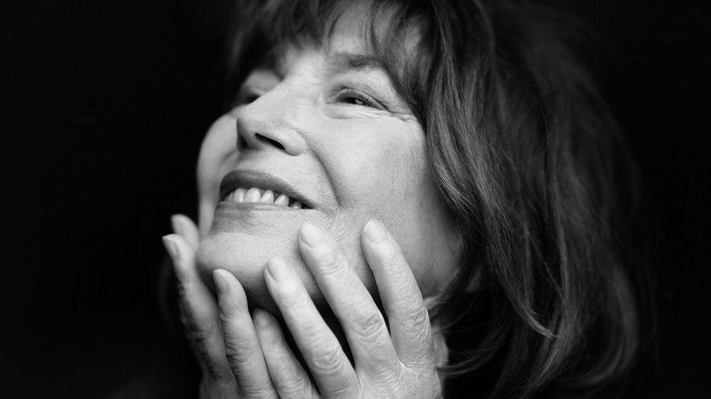 Frau blickt lächelnd nach links oben –  Jane Birkin auf einem Schwarz-Weiß-Foto