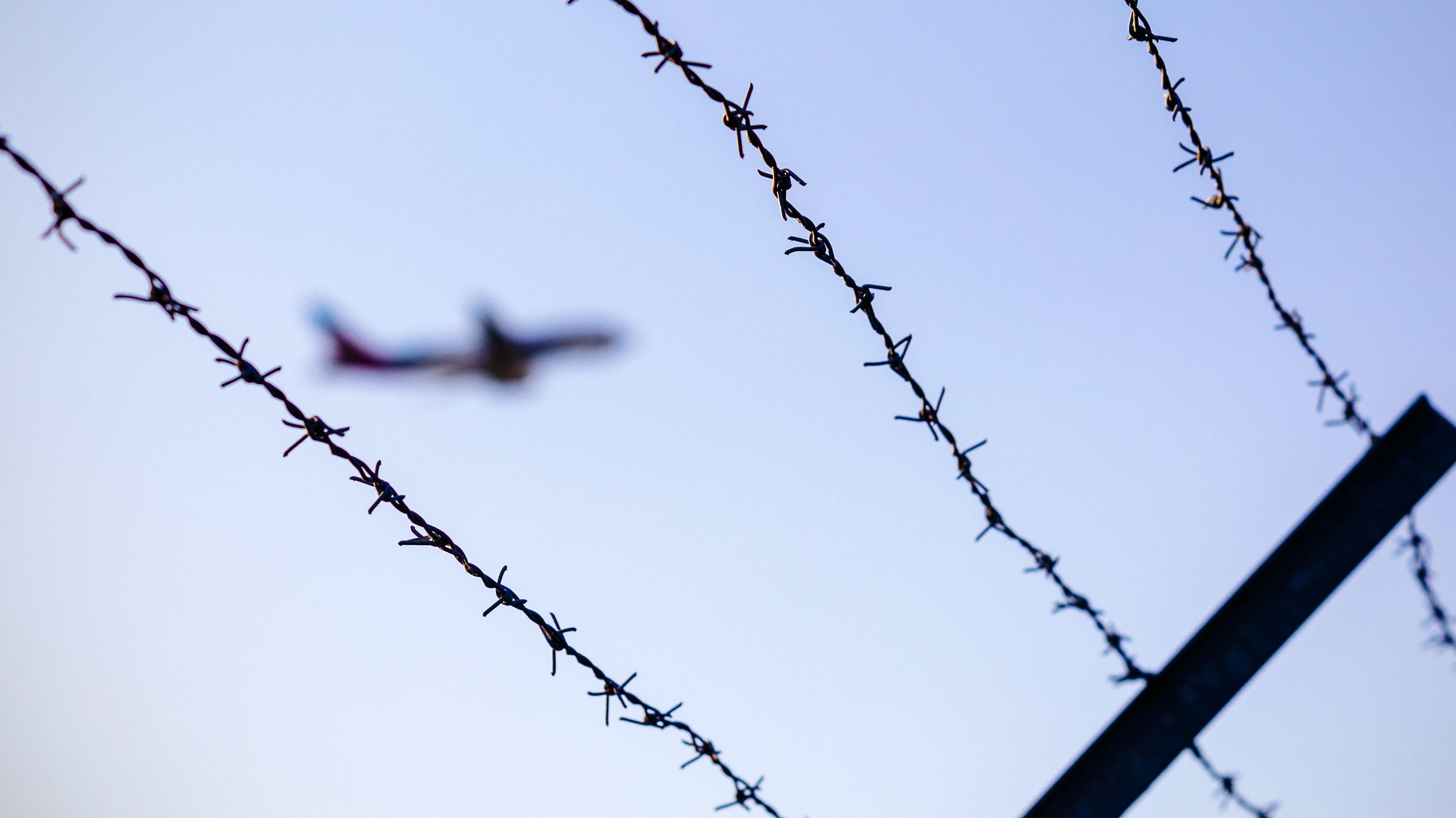 Symbolbild: Flugzeug hinter Stacheldraht. Abschiebung von Flüchtlingen ohne Asylrecht.