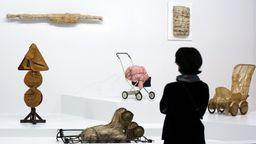Eine Frau mit Rückenansicht, die ein eingepacktes Schild, einen eingpackter Kinderwagen, einen eingepackten Stuhl  betrachtet  | Bild:dpa/picture-alliance