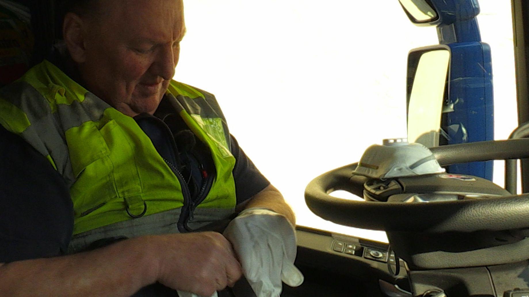Lkw-Fahrer Peter Buchwieser zieht sich im Führerhaus Sicherheitshandschuhe an. Die Schutzmaske liegt auf dem Lenkrad.
