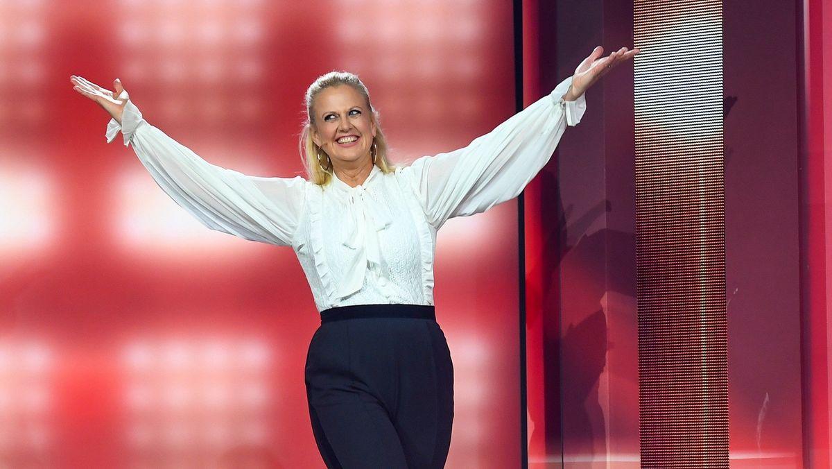 Entertainerin Barbara Schöneberger betritt mit ausgebreiteten Armen eine Bühne vor roter Kulisse