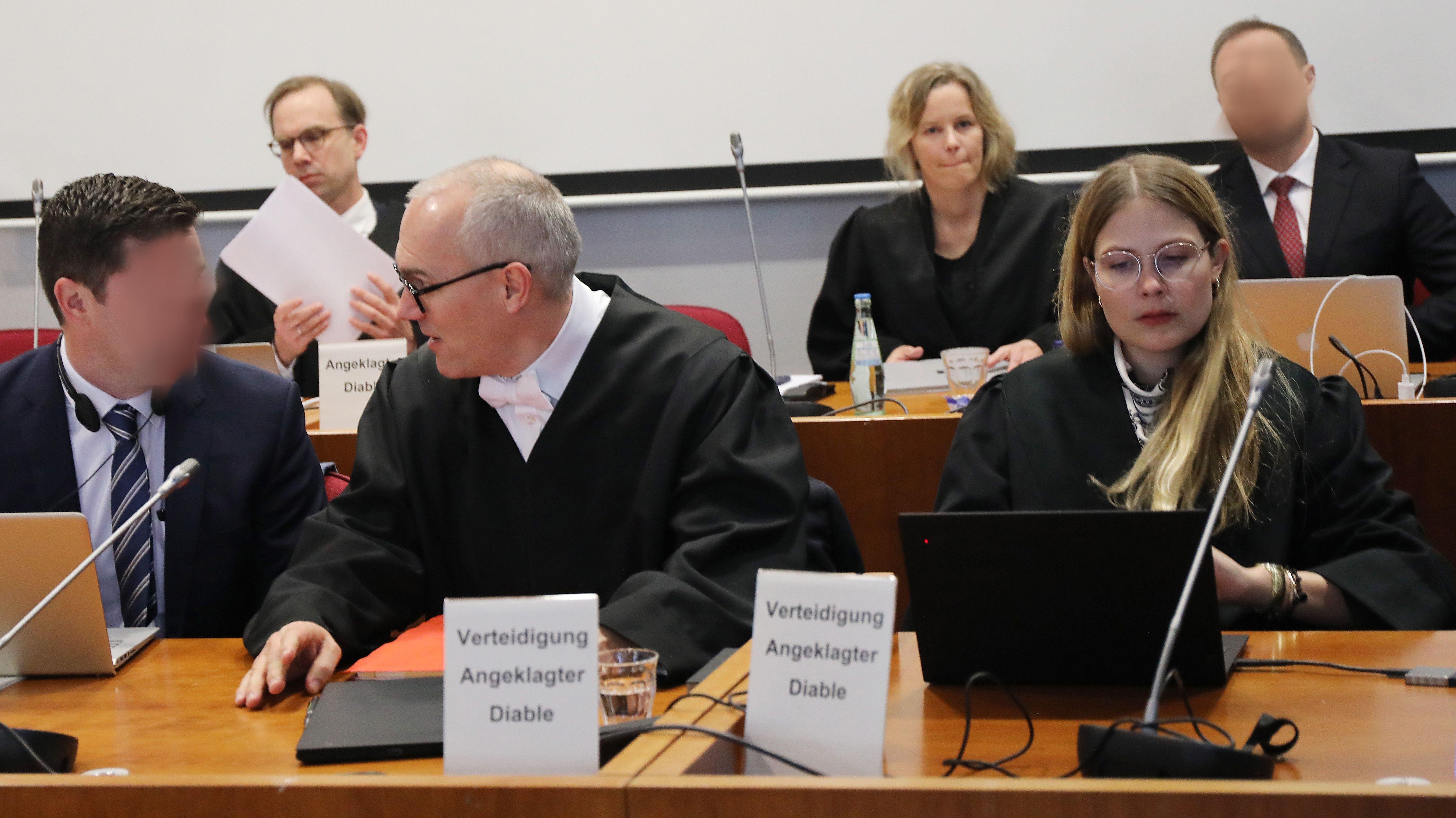 Die Angeklagten (l) und (hinten r) sitzen im Landgericht neben ihren Anwälten.