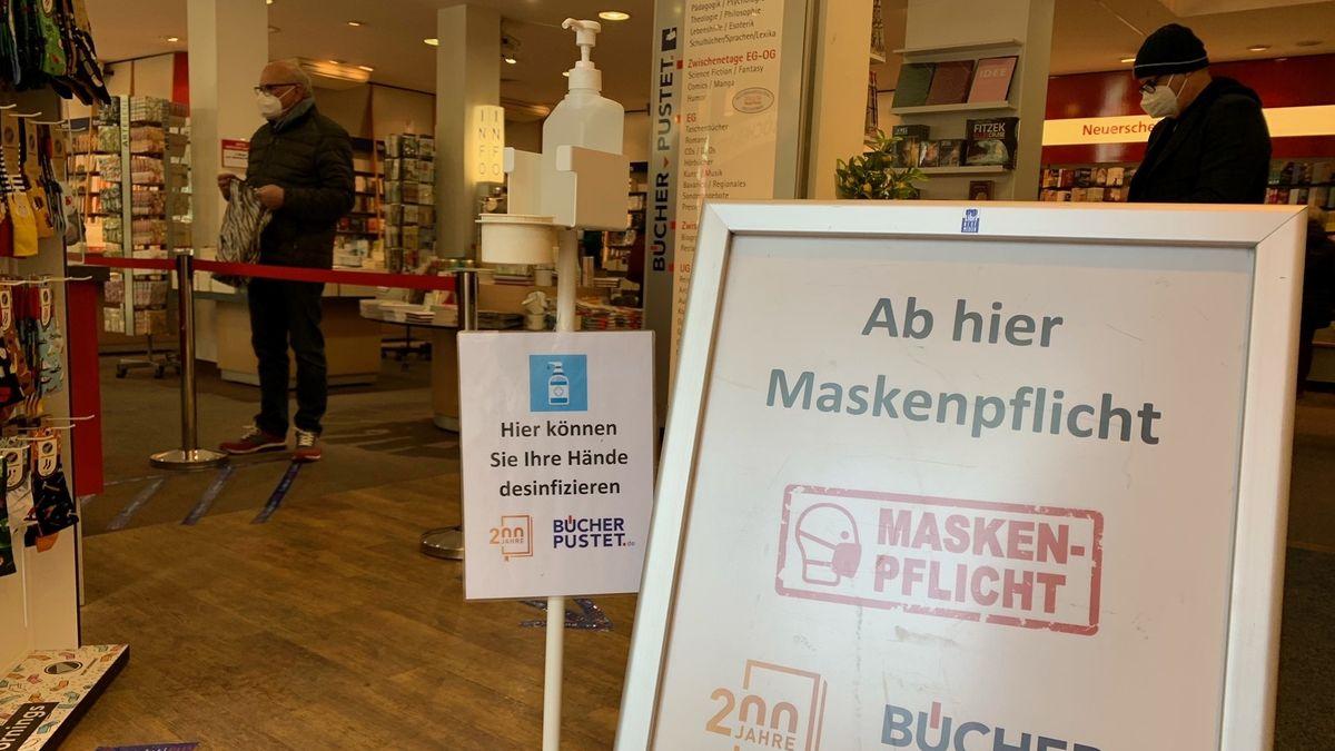 Bild vom Eingang einer Buchhandlung mit Hinweisschildern