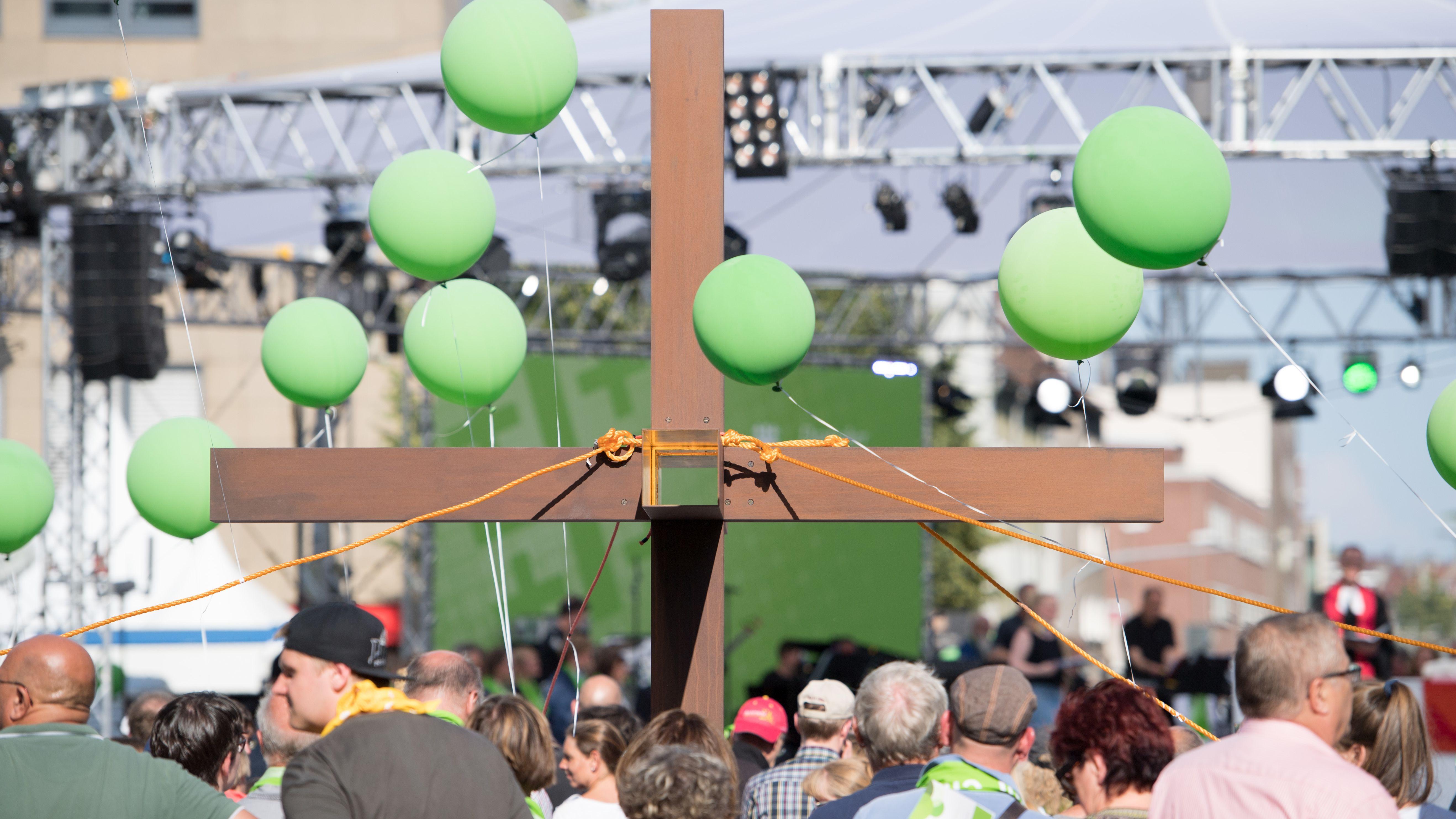 Besucher des Kirchentags vor einem Holzkreuz.