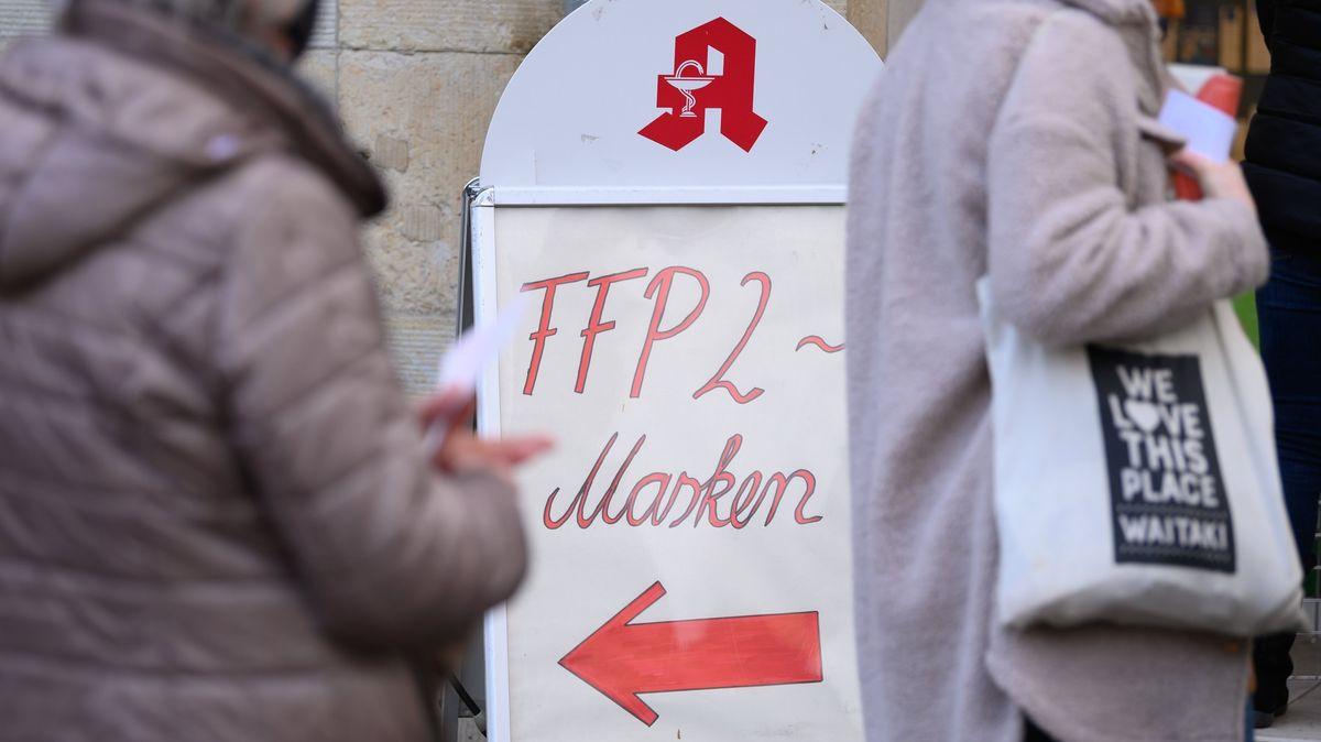 Kunden stehen vor einer Apotheke und warten auf die Ausgabe von FFP2-Masken