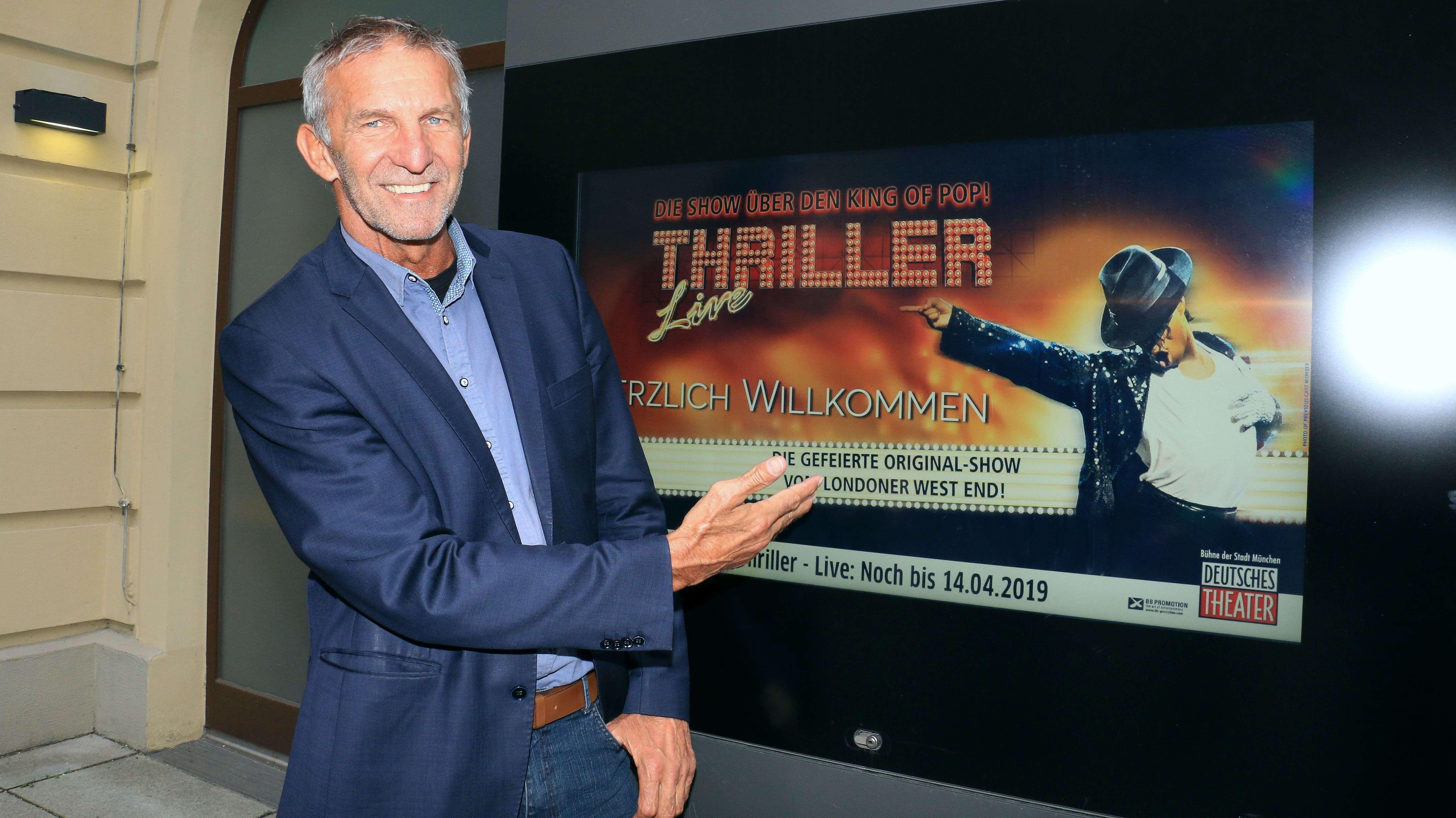Geschäftsführer des Deutschen Theaters vor Werbeplakat