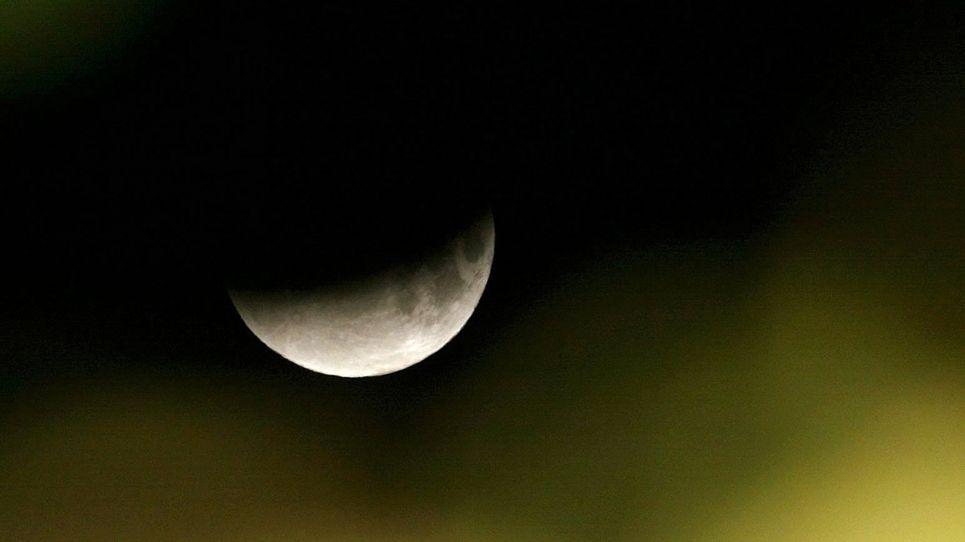 Foto einer partiellen Mondfinsternis: Der Erdschatten schiebt sich teilweise über den Mond und verdeckt ein Stück der Mondscheibe. Der Vollmond schrumpft scheinbar zur Mondsichel.