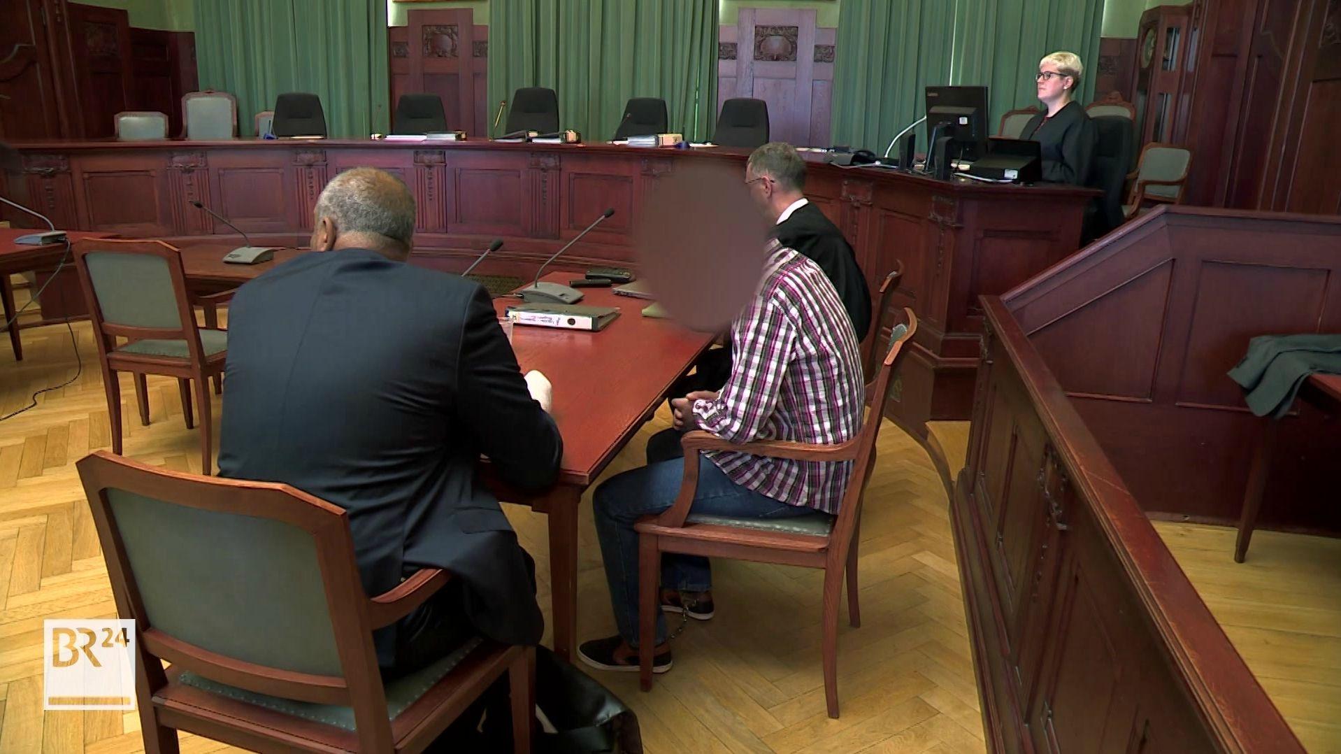 Im Gerichtssaal im Landgericht Bayreuth sitzen der Angeklagte, sein Übersetzer und sein Verteidiger an einem Tisch.