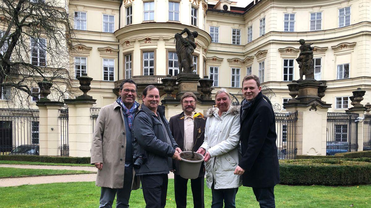 Vier Personen halten einen Eimer mit einer eingepflanzten Eiche, dahinter das Gebäude der Deutschen Botschaft in Prag.