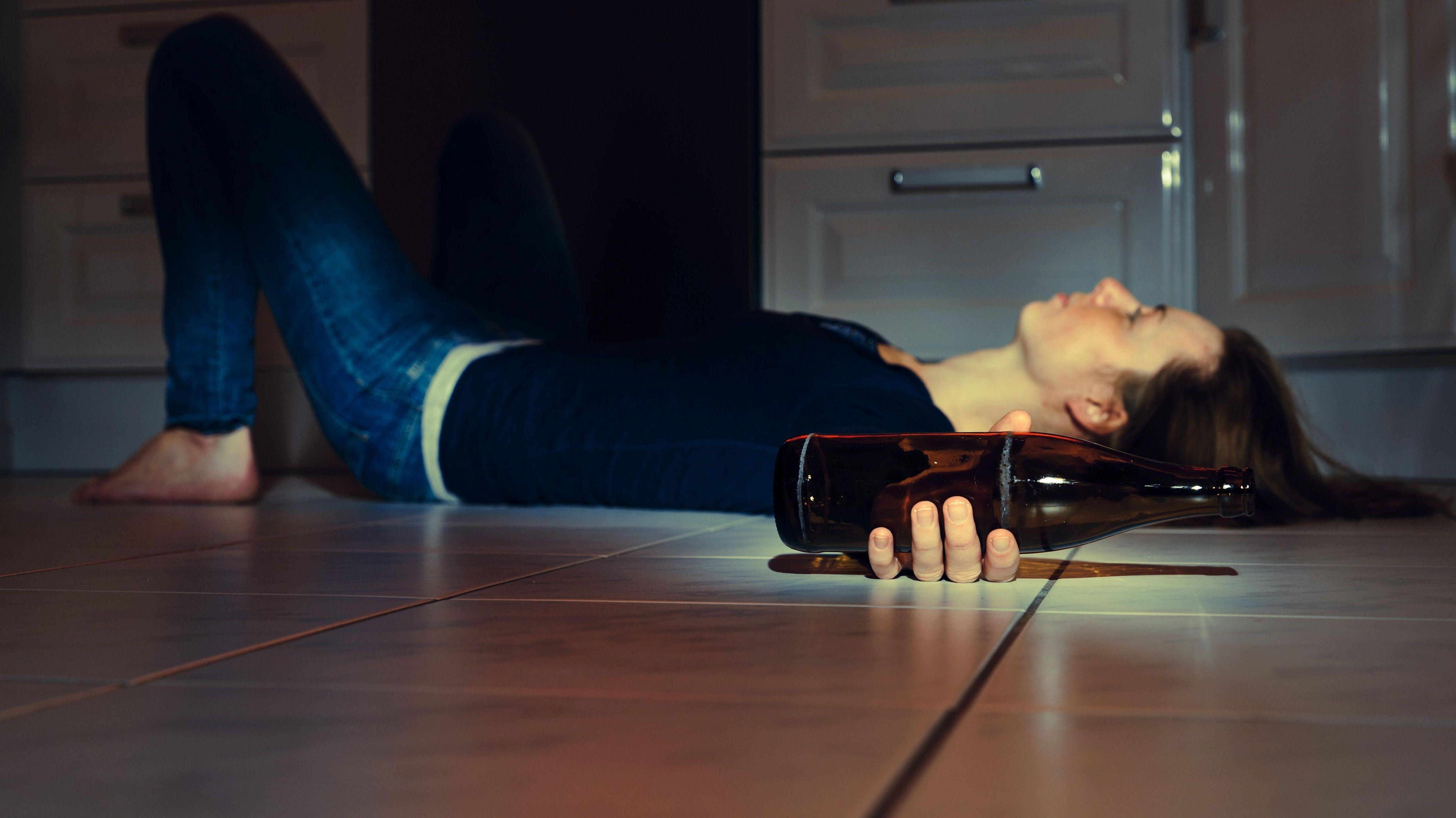 Symbolbild: Eine Frau mit Bierflasche in der Hand liegt auf dem Fußboden.