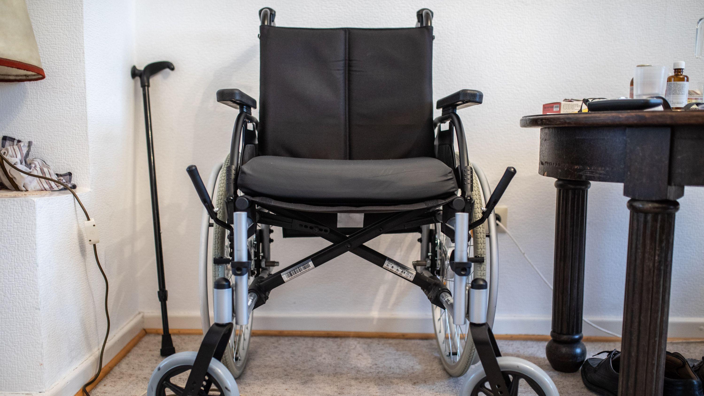 Ein Rollstuhl steht in einer Wohnung an einer Wand