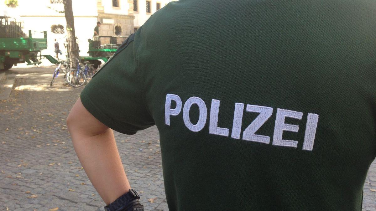 """Polizist mit grünem Poloshirt und Rückenaufschrift """"Polizei"""" (Symbolbild)"""