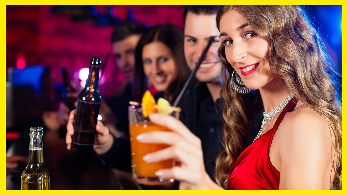 Eine Frau steht mit anderen Menschen in einem Club und hält einen Cocktail in der Hand und lächelt in die Kamera.