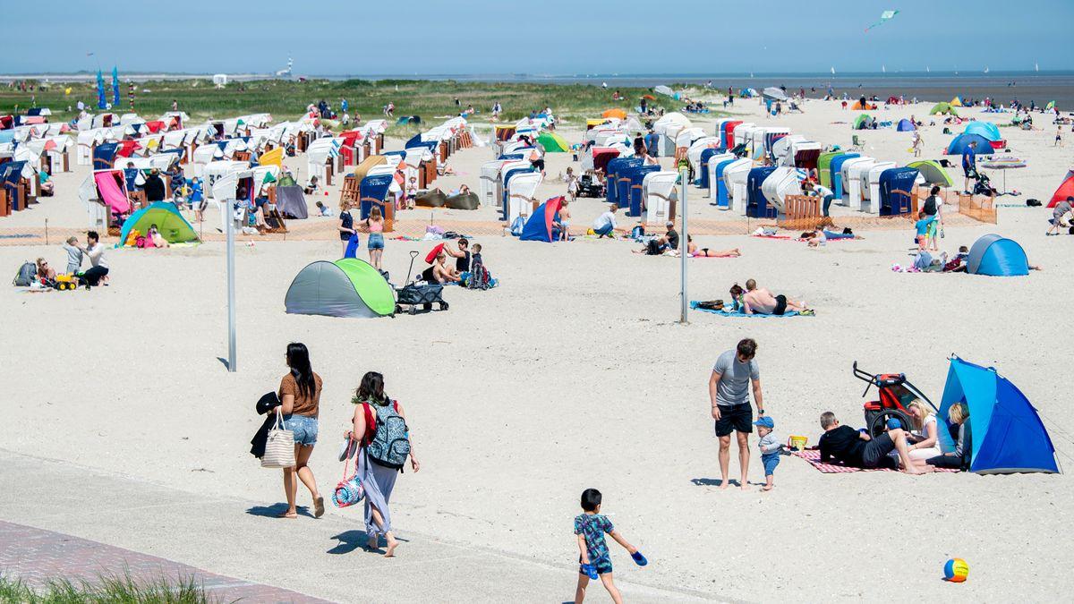 Touristen sitzen am 30. Mai am Strand von Schillig im Landkreis Friesland