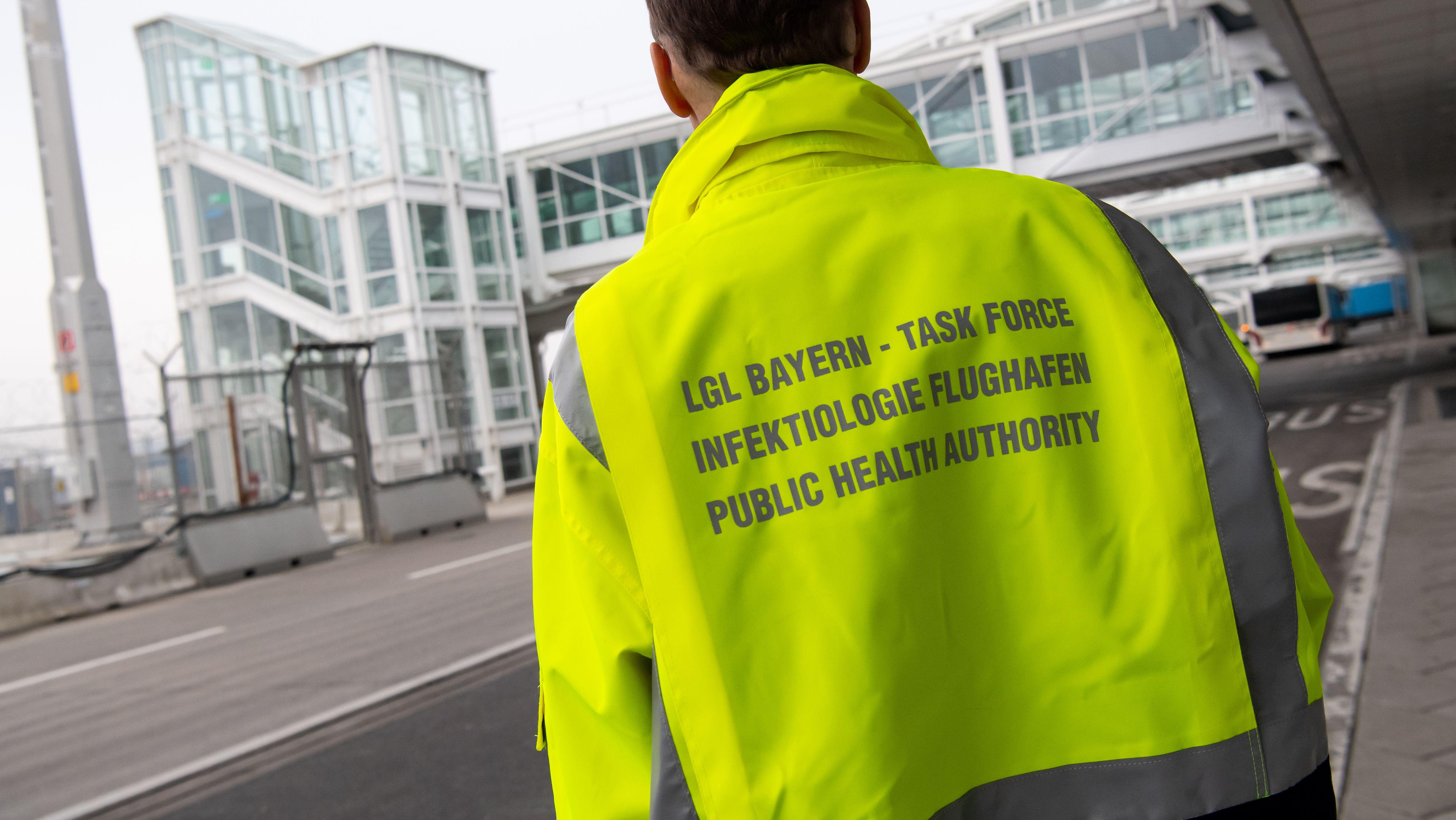 """""""Task Force - Infektiologie Flughafen"""" steht auf der Jacke eines Mitarbeiters der """"Task-Force Infektiologie» am Flughafen München."""