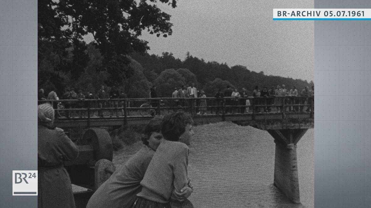 Menschen stehen auf Brücke und warten auf Flutwelle