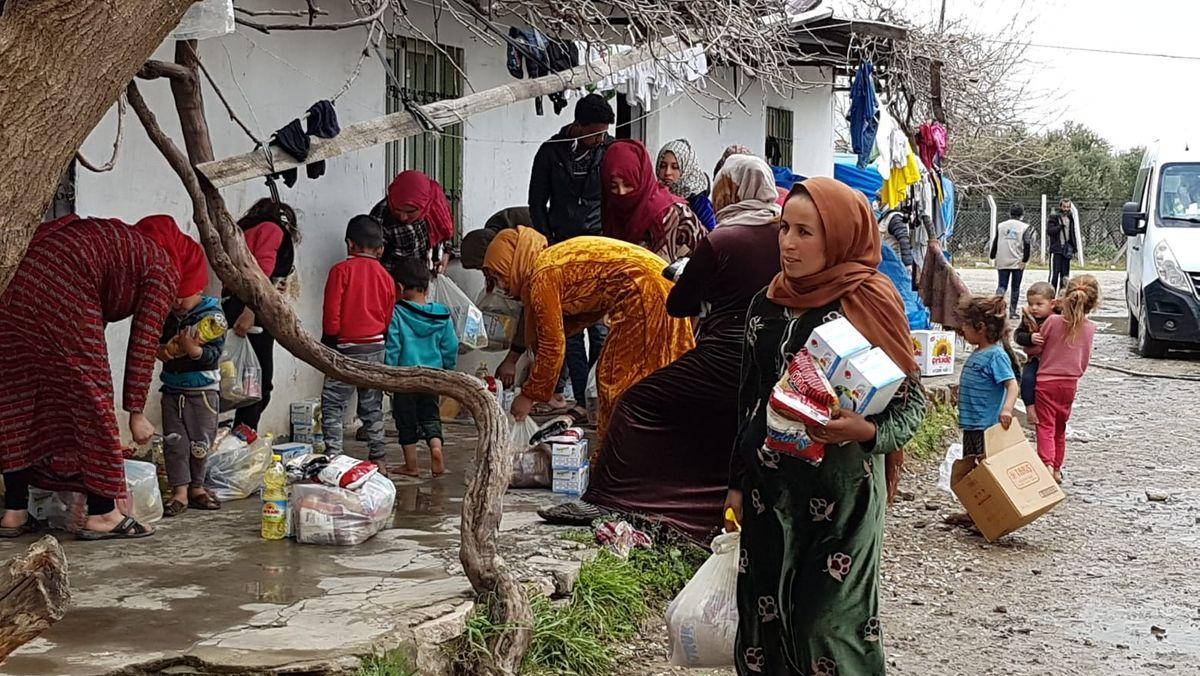 Flüchtlingscamp in türkischen Izmir - Frauen und Kinder in bunten Tüchern holen Essenpakete ab