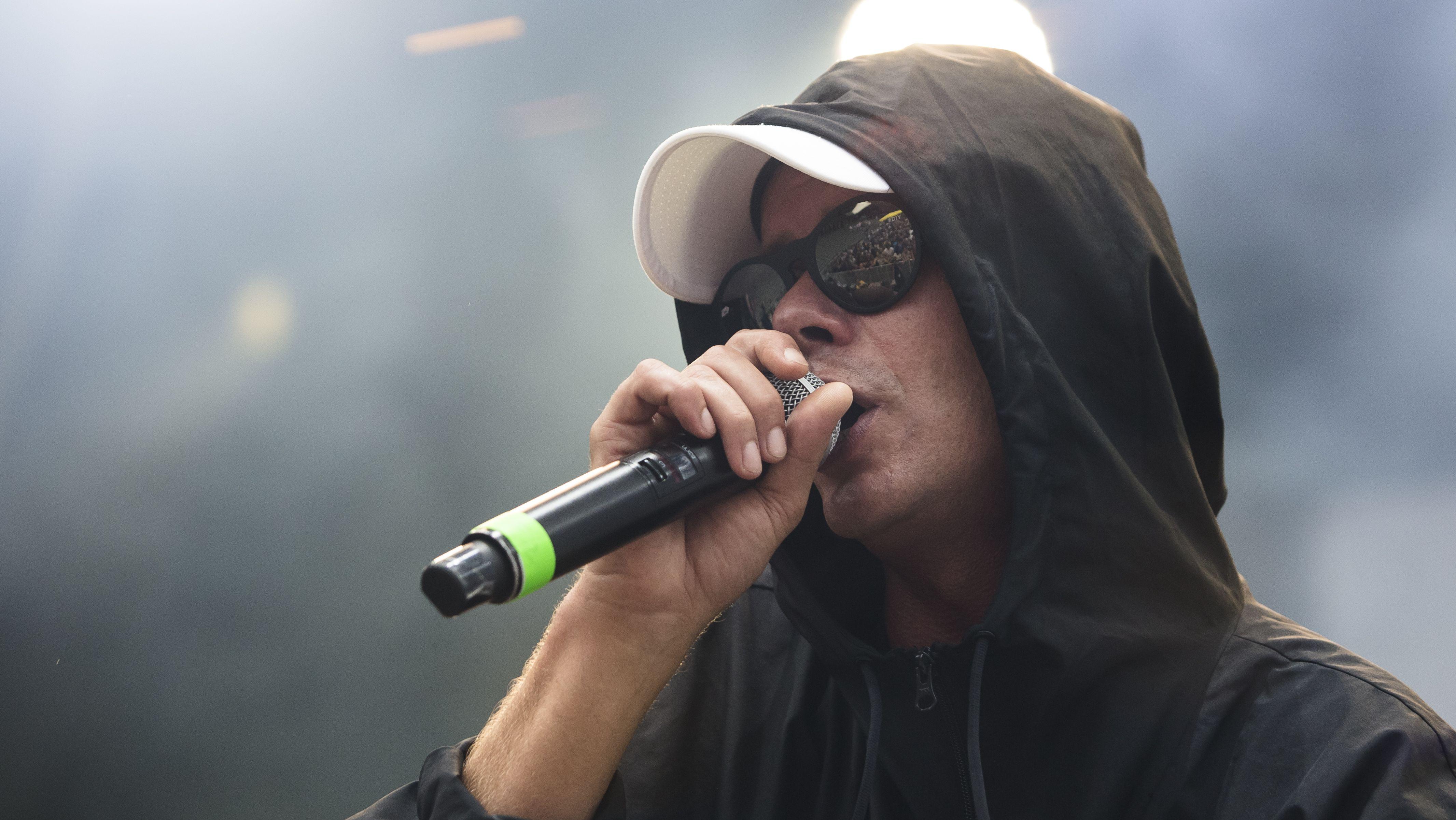 Trettmann in seinem Standardlook: Sonnenbrille vor den Augen, Cap auf dem Kopf und drüber noch eine Kapuze.