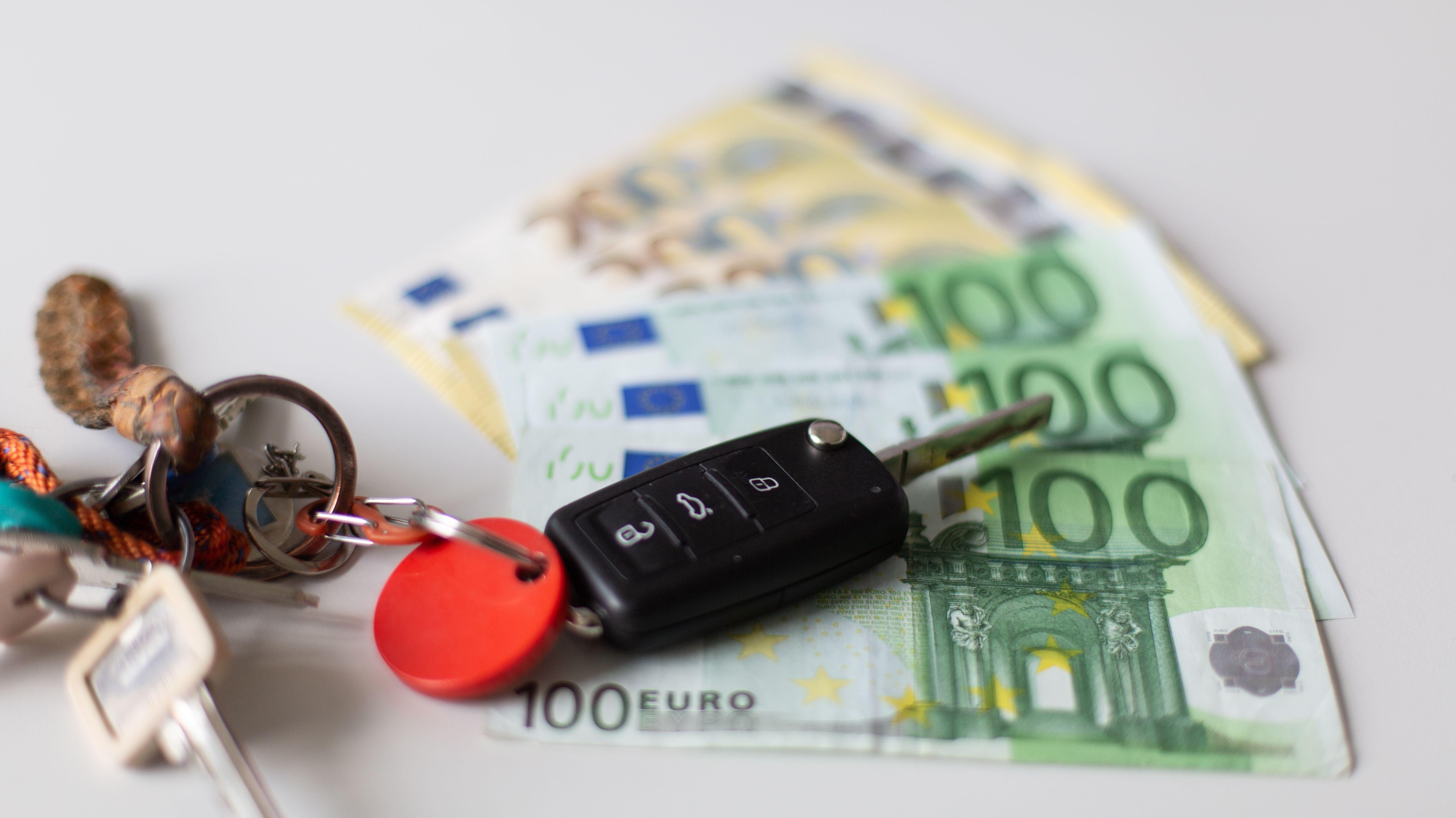 Ein Autoschlüssel auf mehreren aufgefächerten Geldscheinen