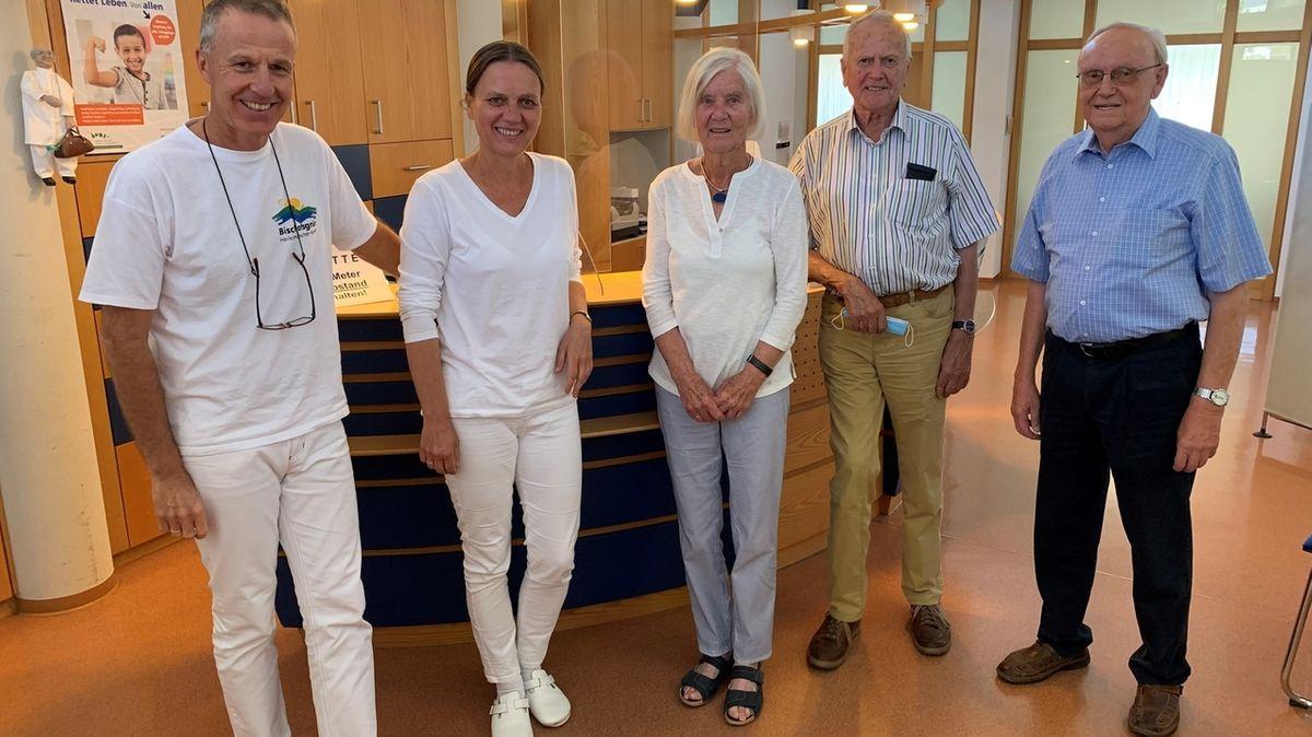Vor dem Empfangstresen ihrer Praxis stehen die Ärzte Michael und Thekla Hieber, Doris und Karl-Herbert Schmidt und der langjährige Patient Johann Ackermann.