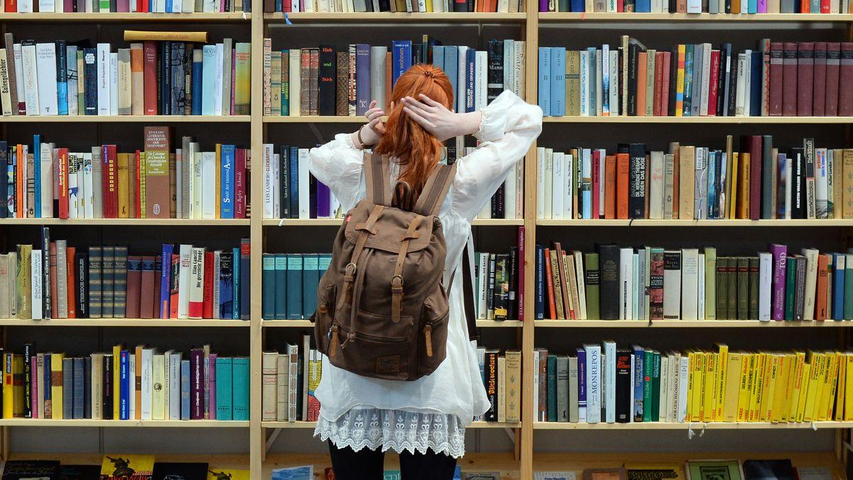 Eine Besucherin steht 2017 auf der Buchmesse Leipzig (Sachsen) an einem Regal mit Büchern.