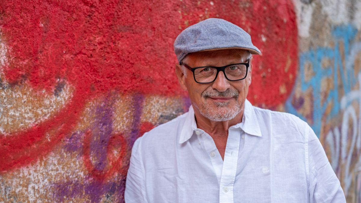 Liedermacher Konstantin Wecker steht lächelnd vor einer Wand mit bunten Graffitis. Er trägt Schirmmütze und ein weißes Hemd.