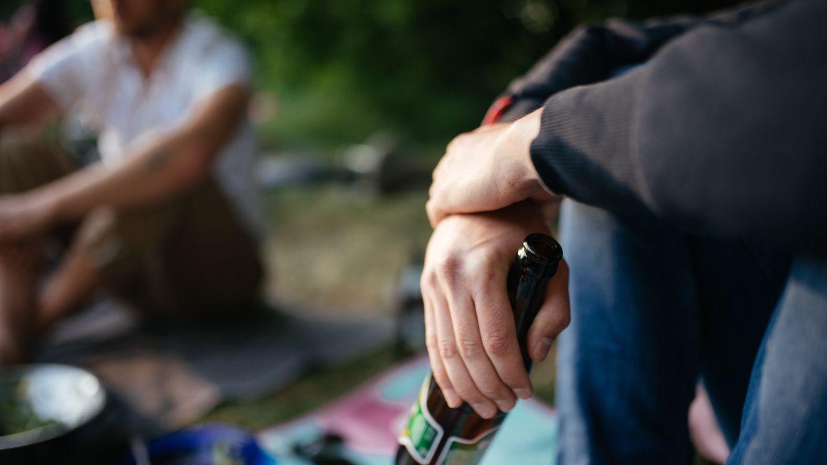 Ein junger Mann mit Bierflasche in der Hand.