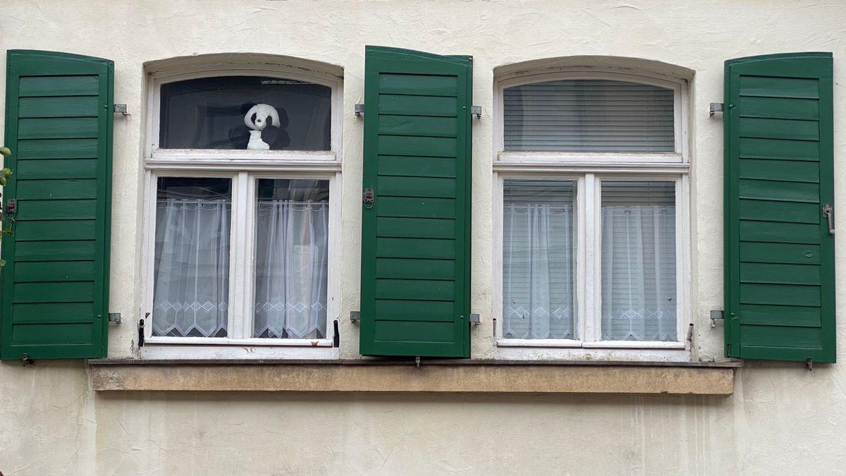In einem Fenster eines Hauses in Ebern sitzt ein Pandabär aus Plüsch.