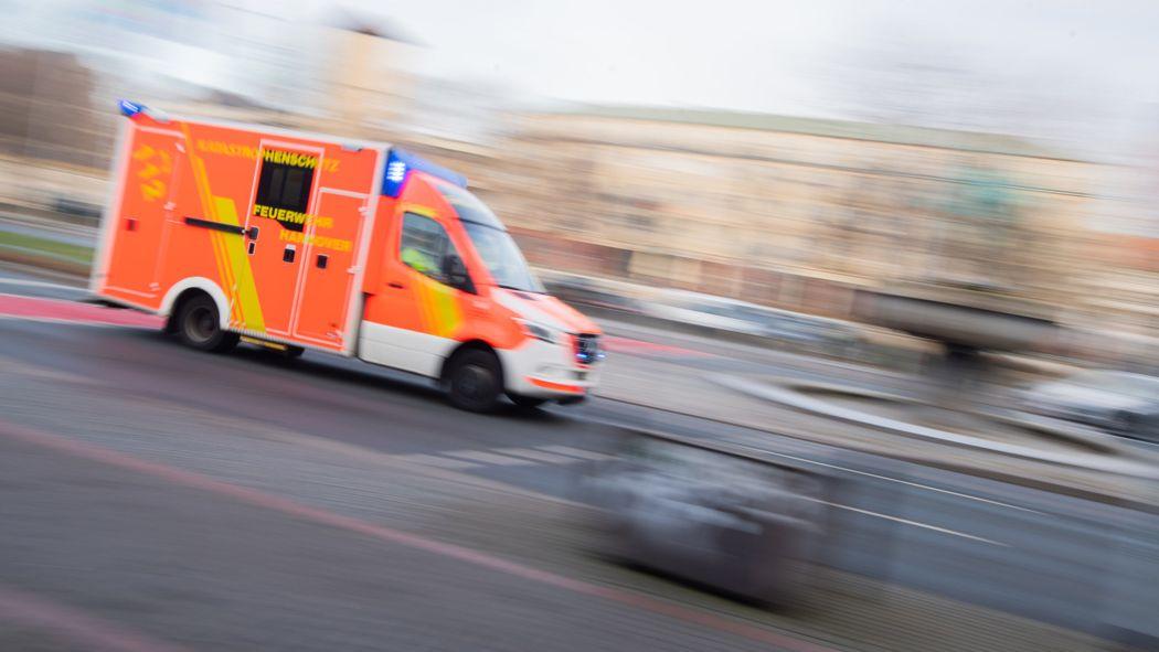 Ein Rettungswagen fährt mit Blaulicht durch eine Innenstadt.