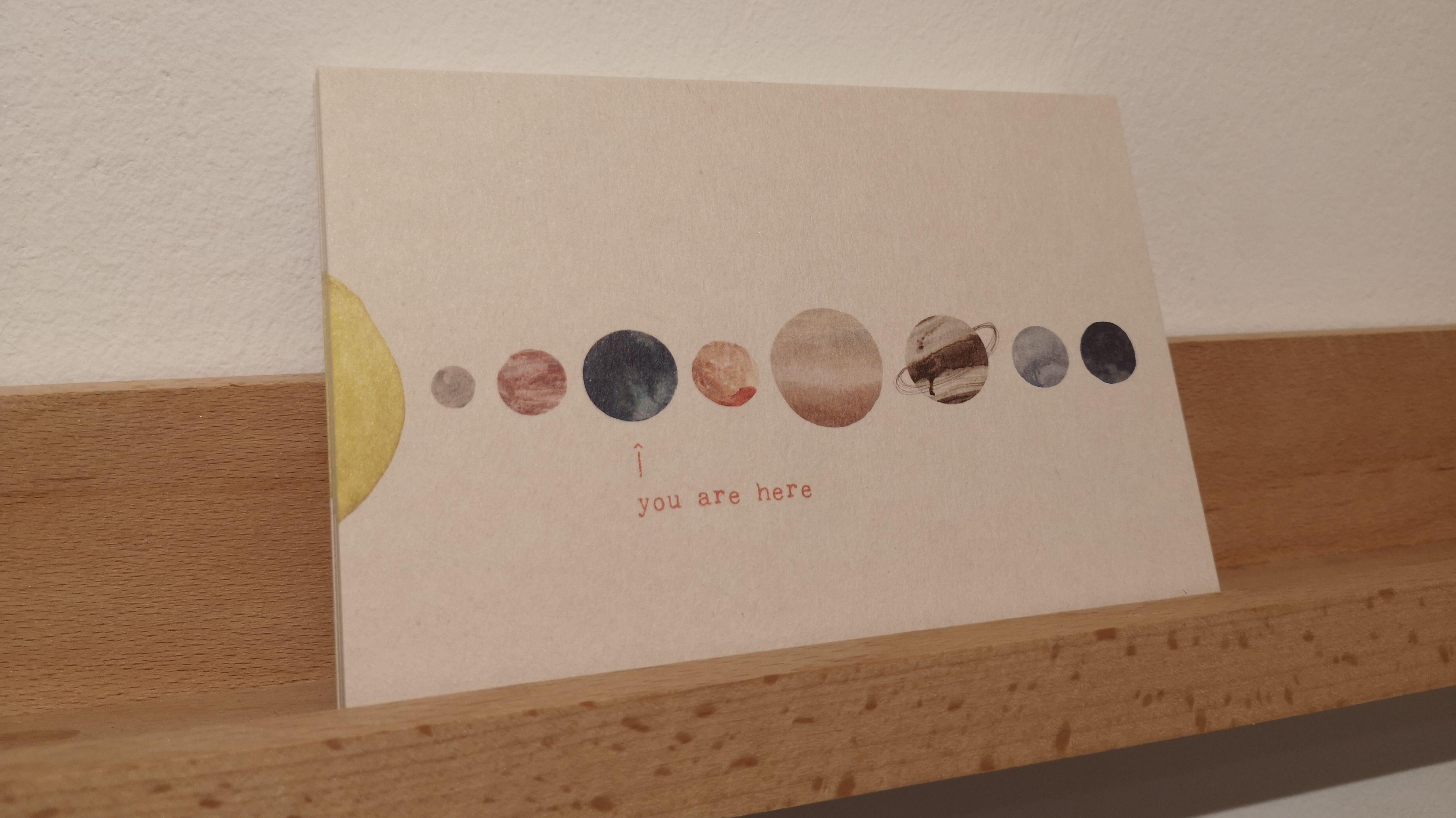 Eine Postkarte. Darauf zu sehen: Die Sonne und acht Planeten. Ein kleiner Pfeil zeigt auf die Erde. Darunter steht: you are here.